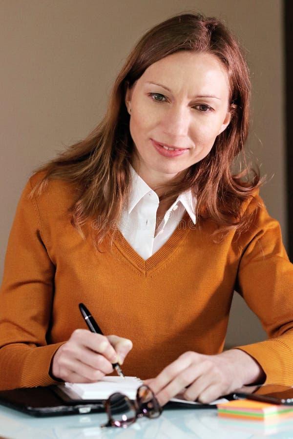 Mujer inteligente que toma notas del negocio foto de archivo