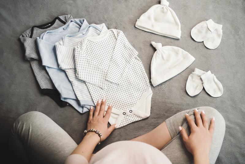 Mujer irreconocible embarazada que se sienta con ropa del bebé Visión superior fotos de archivo