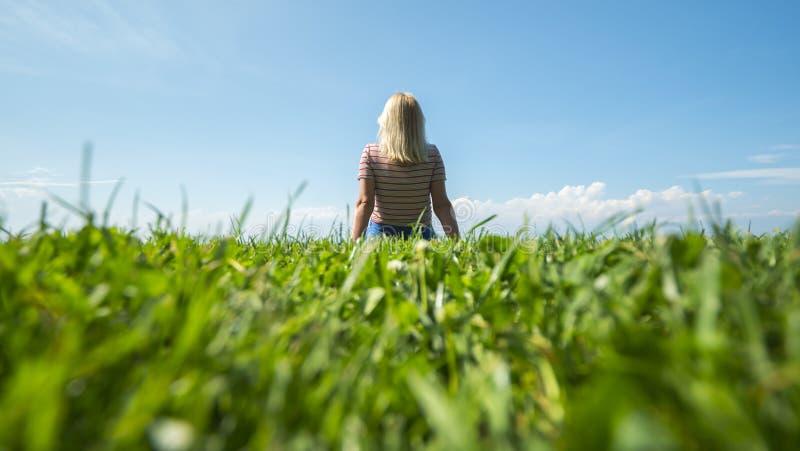 Mujer irreconocible joven que se sienta en un césped verde foto de archivo
