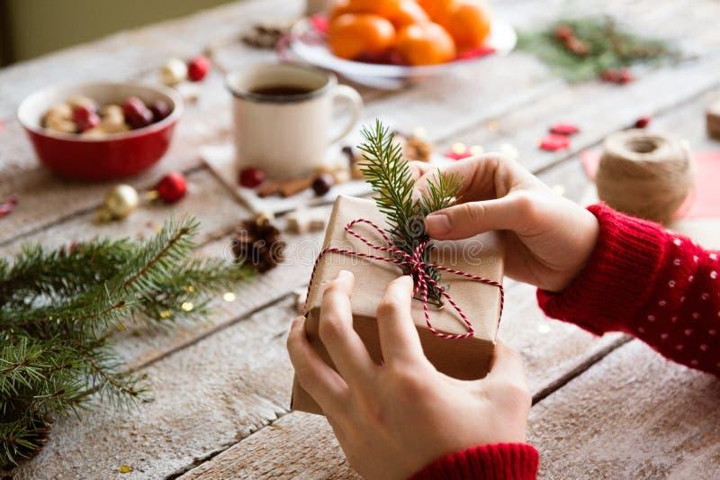 Mujer irreconocible que envuelve y que adorna el regalo de Navidad imagen de archivo