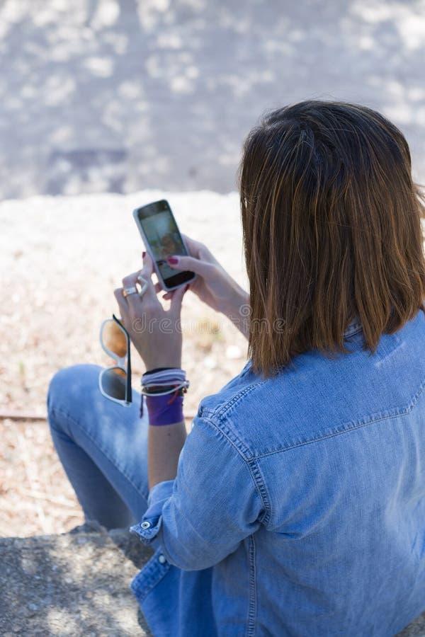 Mujer irreconocible que usa el teléfono celular imágenes de archivo libres de regalías