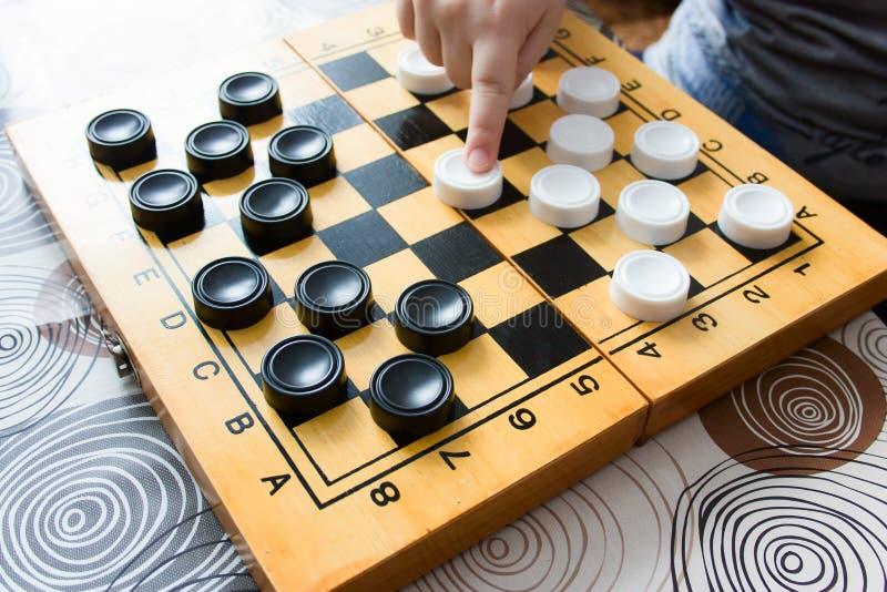 Mujer irreconocible y niño que juegan a ajedrez en casa imágenes de archivo libres de regalías