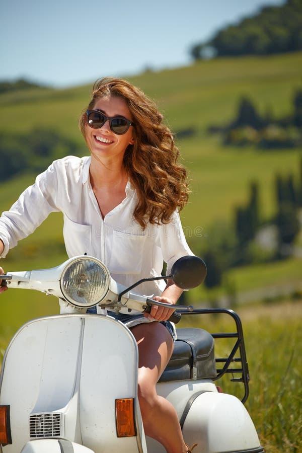 Mujer italiana hermosa joven que se sienta en una vespa imagen de archivo