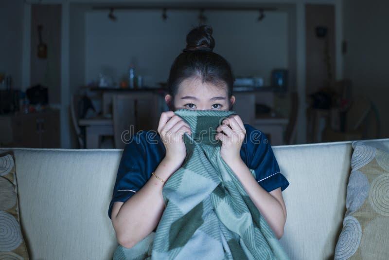 Mujer japonesa asiática feliz y alegre hermosa joven que mira la película de la comedia de la TV o la demostración hilarante que  imagenes de archivo