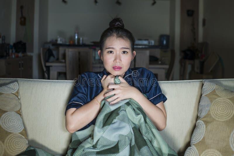 Mujer japonesa asiática feliz y alegre hermosa joven que mira la película de la comedia de la TV o la demostración hilarante que  fotos de archivo