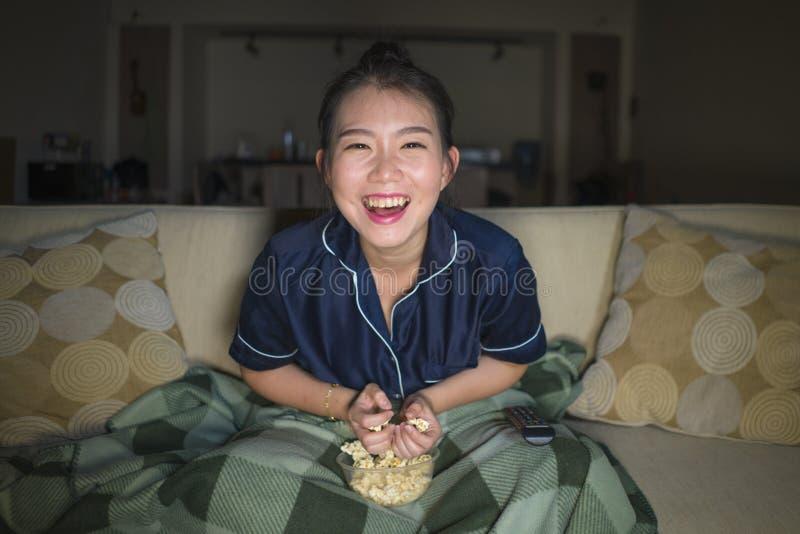 Mujer japonesa asiática feliz y alegre hermosa joven que mira la película de la comedia de la TV o la demostración hilarante que  fotografía de archivo