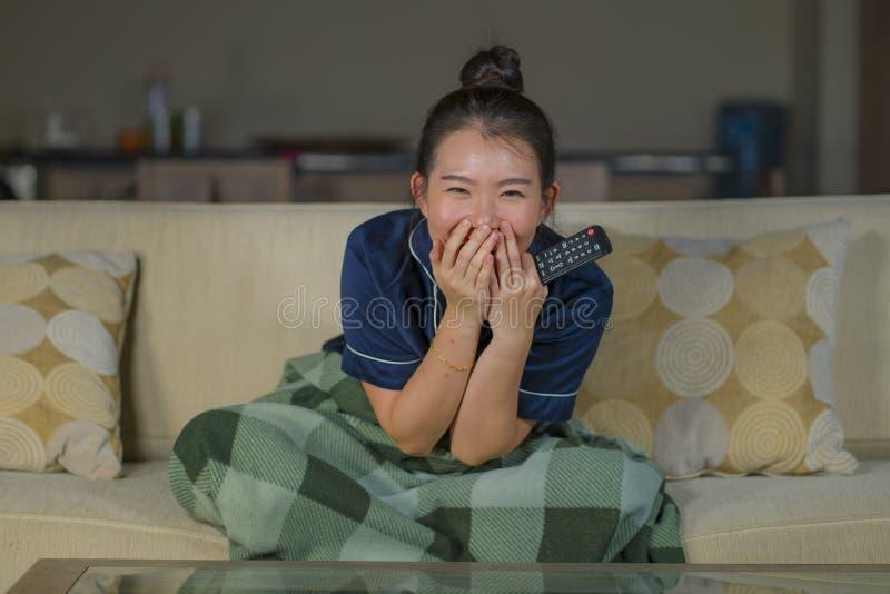 Mujer japonesa asiática feliz y alegre hermosa joven que mira la película de la comedia de la TV o la demostración hilarante que  fotos de archivo libres de regalías