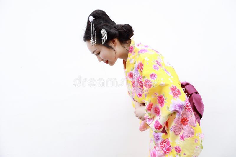 Mujer japonesa asiática tradicional con el arco respetuoso del kimono en fondo blanco aislado fotografía de archivo