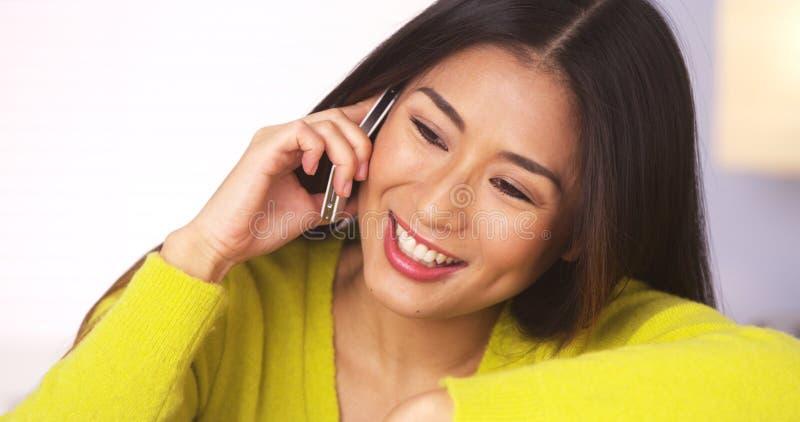Mujer japonesa feliz que habla en smartphone imágenes de archivo libres de regalías
