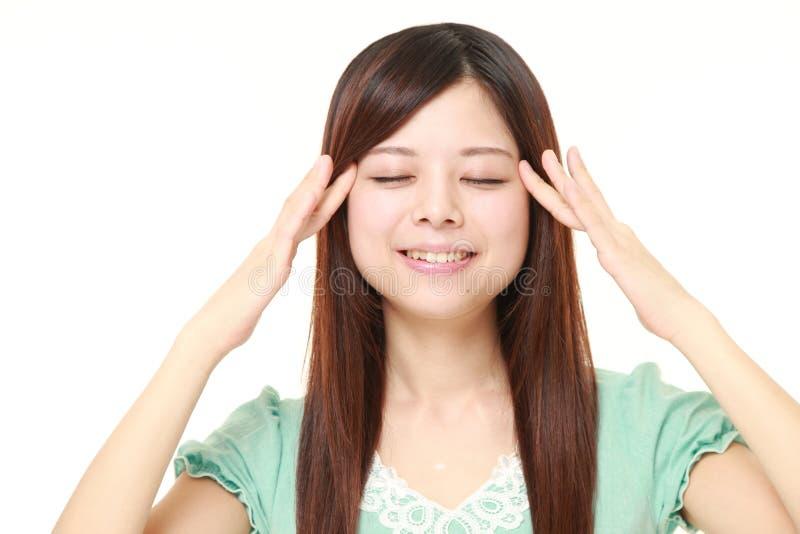 Mujer japonesa joven que hace el masaje principal del uno mismo foto de archivo libre de regalías