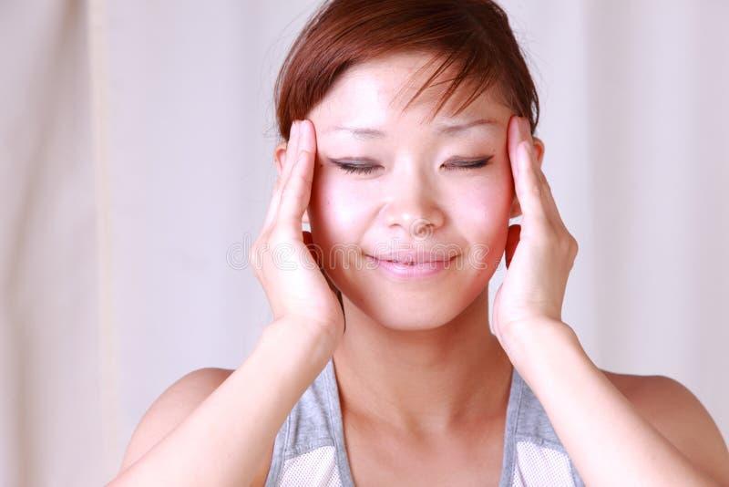 Mujer japonesa joven que hace un massage  de la cara del uno mismo fotos de archivo