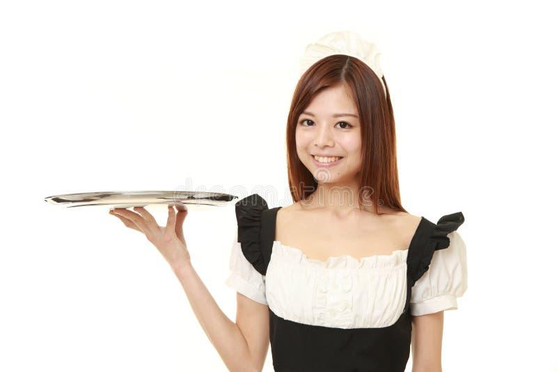 Mujer japonesa joven que lleva el traje francés de la criada con la bandeja imágenes de archivo libres de regalías