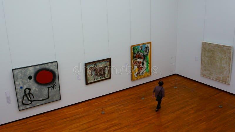 Mujer japonesa mayor en una exposición de pinturas de los artistas del siglo XX imagen de archivo libre de regalías
