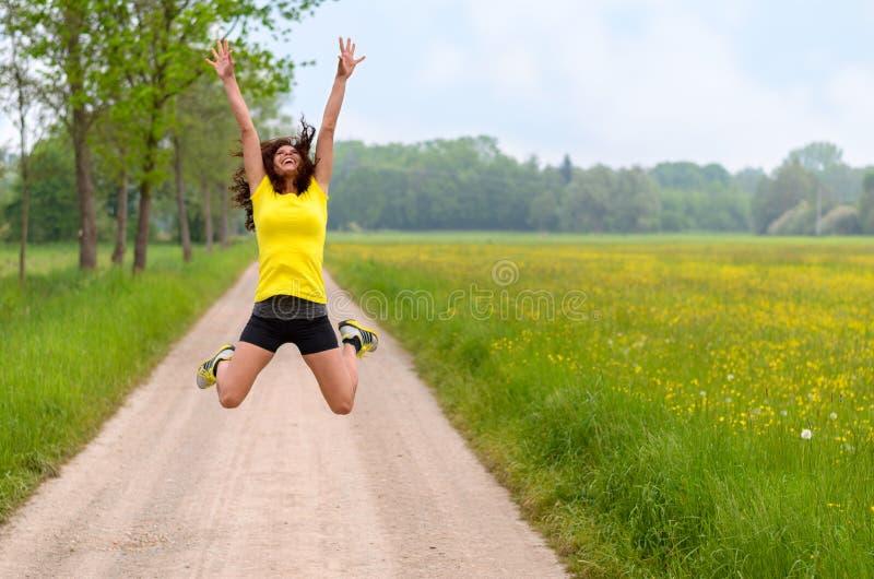 Mujer joven ágil enérgica que salta para la alegría imagenes de archivo