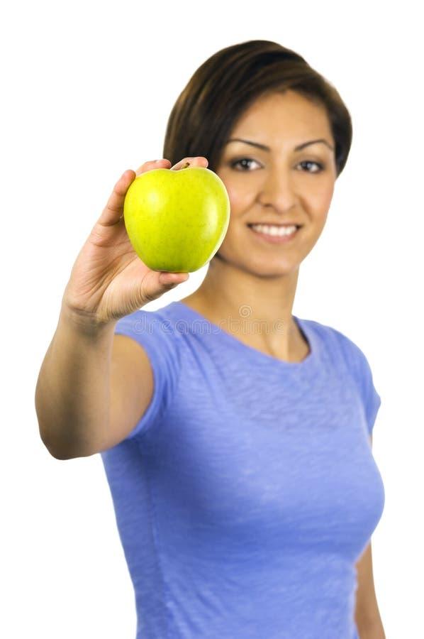 Mujer joven, étnica que sostiene una manzana verde foto de archivo