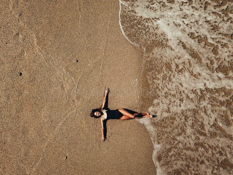 Mujer joven aérea de la visión superior que miente en la playa y las ondas de la arena foto de archivo libre de regalías