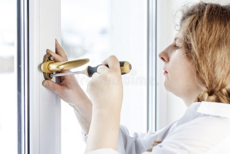 Mujer joven 30 años desatornille el tornillo con un destornillador I& x27; m que va a fijar la pluma sobre el vidrio foto de archivo