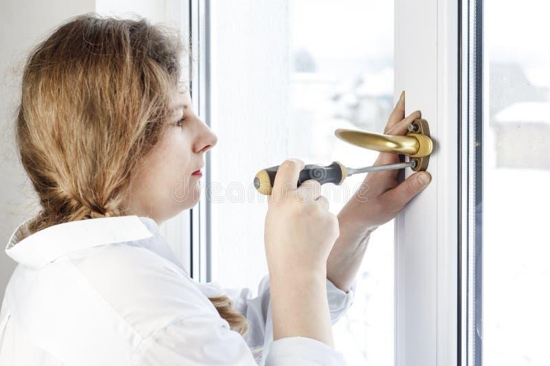 Mujer joven 30 años desatornille el tornillo con un destornillador I& x27; m que va a fijar la pluma sobre el vidrio foto de archivo libre de regalías