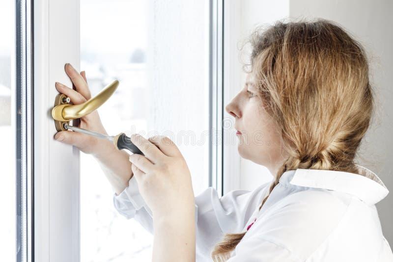 Mujer joven 30 años desatornille el tornillo con un destornillador I& x27; m que va a fijar la pluma sobre el vidrio imagen de archivo