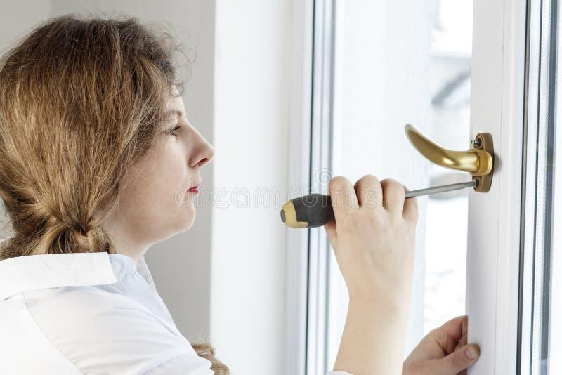 Mujer joven 30 años desatornille el tornillo con un destornillador I& x27; m que va a fijar la pluma sobre el vidrio fotografía de archivo
