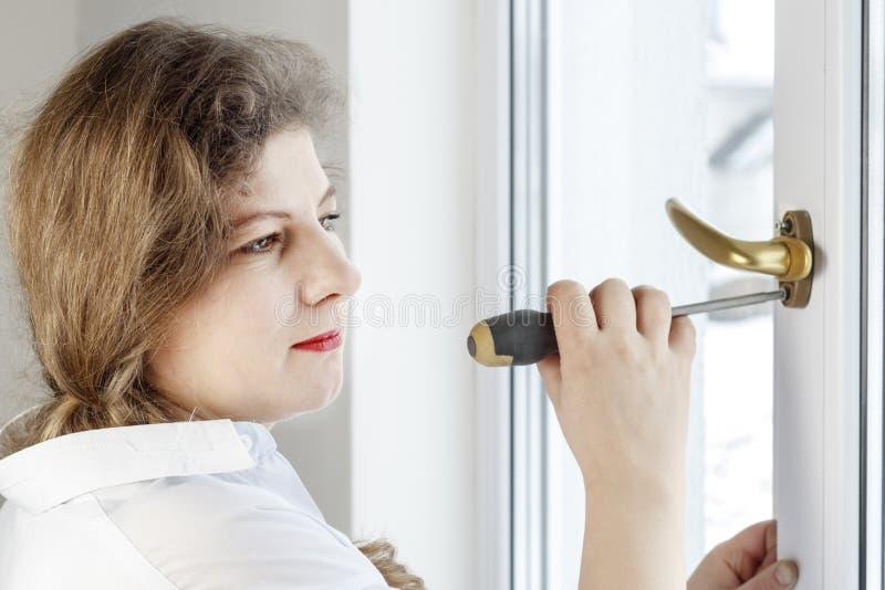 Mujer joven 30 años desatornille el tornillo con un destornillador I& x27; m que va a fijar la pluma sobre el vidrio imágenes de archivo libres de regalías