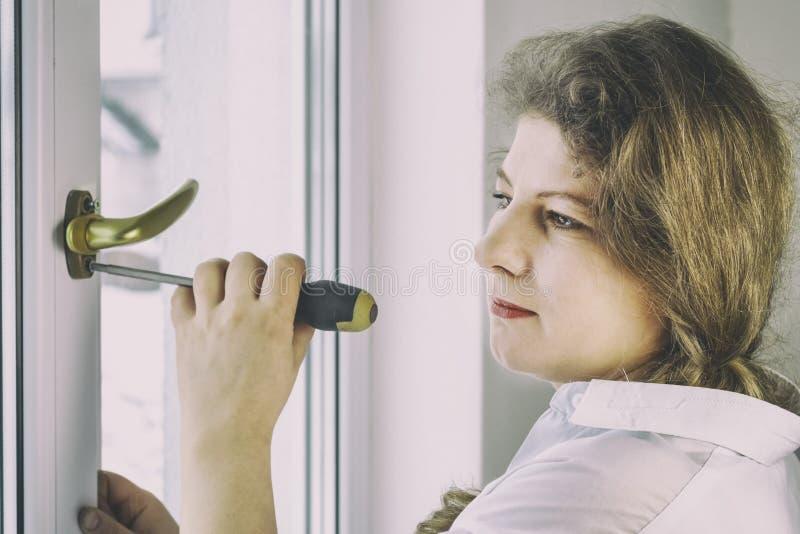 Mujer joven 30 años desatornille el tornillo con un destornillador I& x27; m que va a fijar la pluma sobre el vidrio fotos de archivo