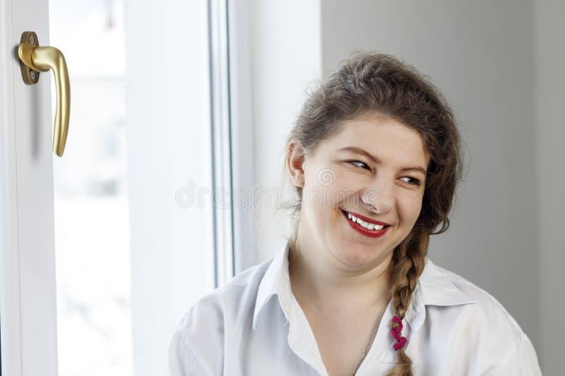 Mujer joven 30 años sonrisas en nosotros el ir a reparar la manija sobre el vidrio fotos de archivo libres de regalías