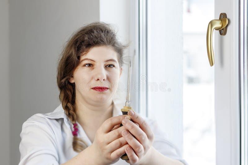 Mujer joven 30 años sorprendido y mirando el destornillador I& x27; m que va a fijar la pluma sobre el vidrio imágenes de archivo libres de regalías