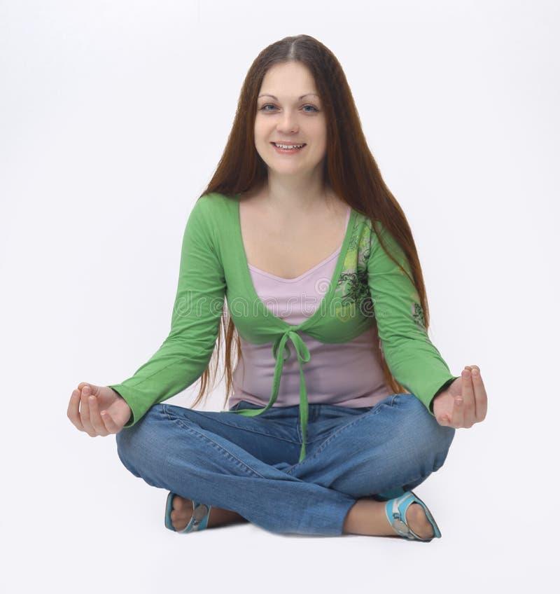 Mujer joven acertada que medita sentarse en el piso foto de archivo libre de regalías