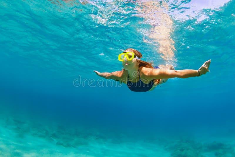 Mujer joven activa en buceo máscara, nadar bajo el agua fotografía de archivo
