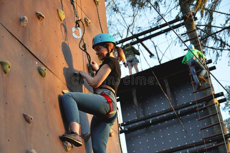 Mujer joven activa en la pared de la roca en centro de deporte imágenes de archivo libres de regalías