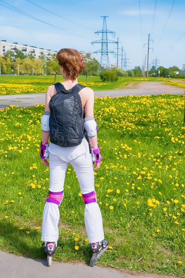 Mujer joven activa en ropa de deportes en pcteres de ruedas Contra brigh fotografía de archivo
