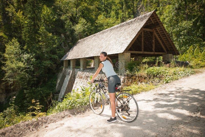 Mujer joven activa que completa un ciclo en bosque en un día de verano caliente fotos de archivo