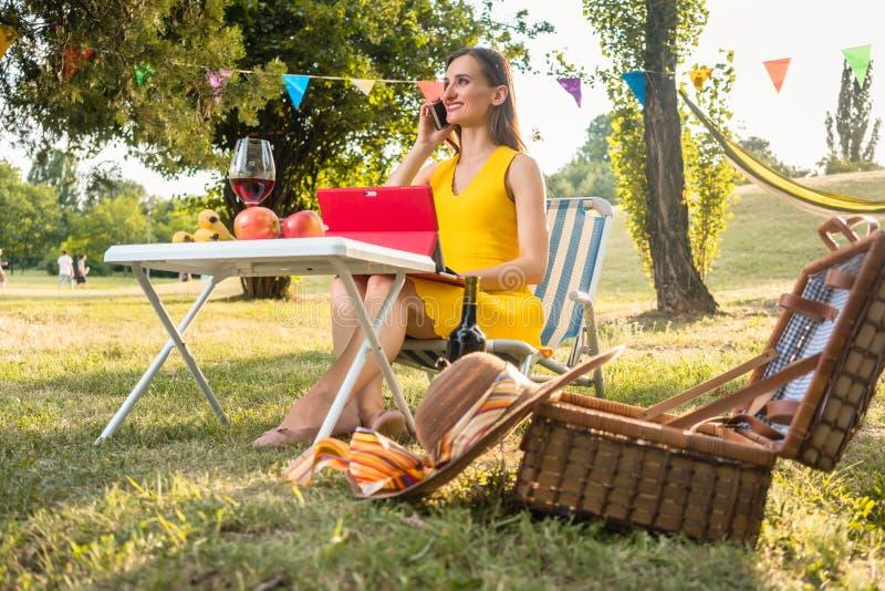 Mujer joven activa que habla en móvil y que usa la tableta durante imagen fotos de archivo libres de regalías