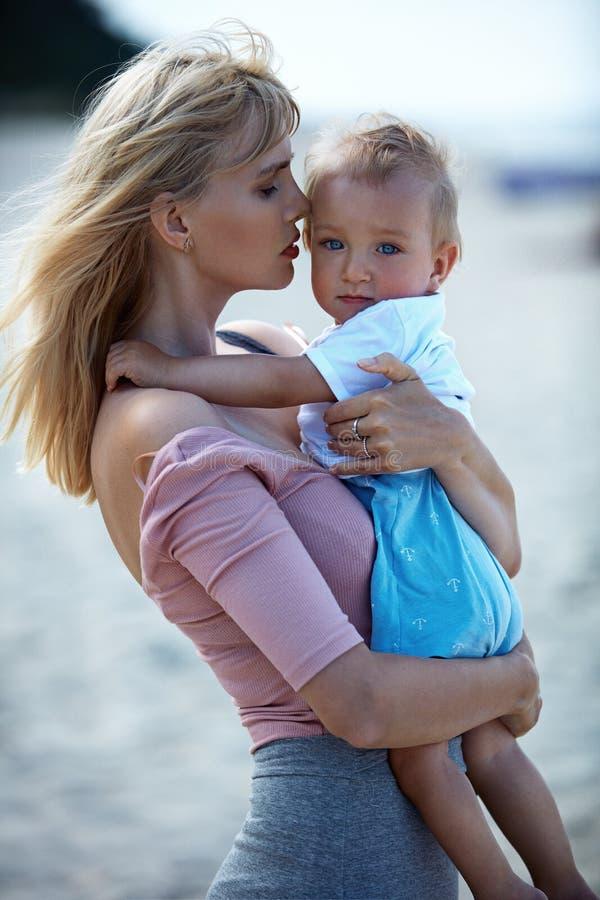 Mujer joven, adorable que lleva a su hijo querido fotos de archivo libres de regalías