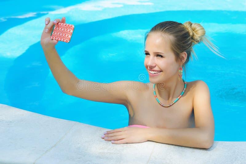 Mujer joven adorable que toma la foto del selfie en la piscina foto de archivo libre de regalías