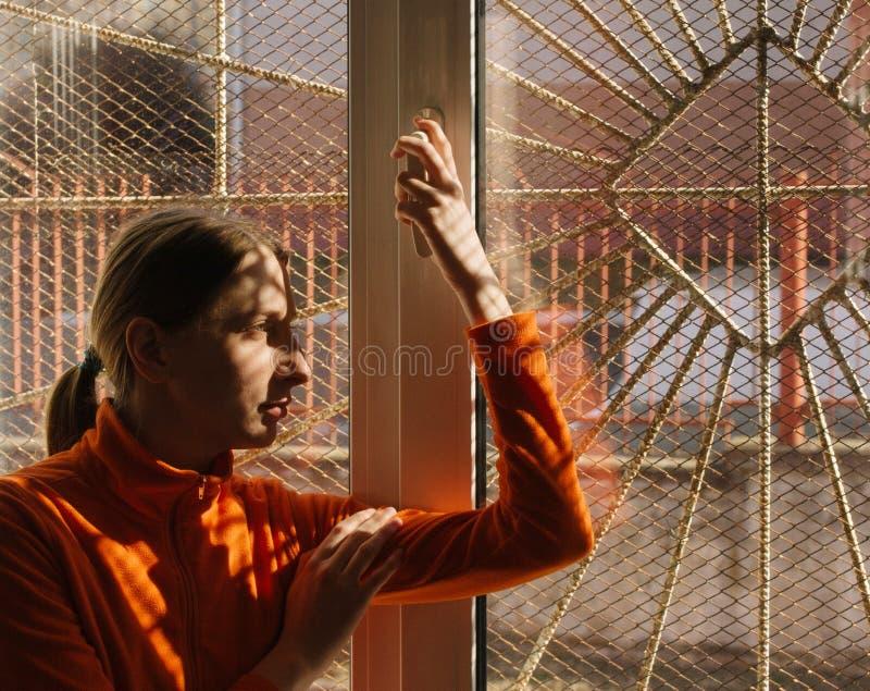 Mujer joven adulta en ropa anaranjada que sonríe y que mira hacia fuera la ventana con las barras y rejilla imágenes de archivo libres de regalías