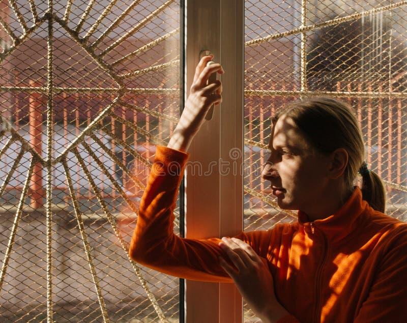 Mujer joven adulta en ropa anaranjada que sonríe y que mira hacia fuera la ventana con las barras y rejilla imagen de archivo