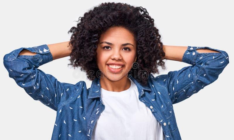 Mujer joven afroamericana bonita vestida en la camiseta blanca y la blusa azul, llevando a cabo las manos en la cabeza, sensación imagen de archivo