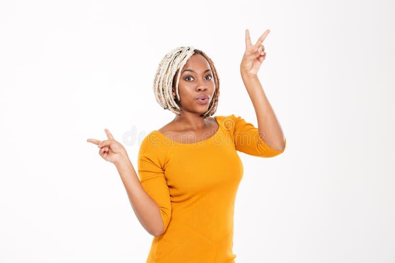 Mujer joven afroamericana emocionada juguetona que muestra el signo de la paz fotos de archivo libres de regalías