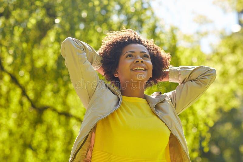 Mujer joven afroamericana feliz en parque del verano foto de archivo