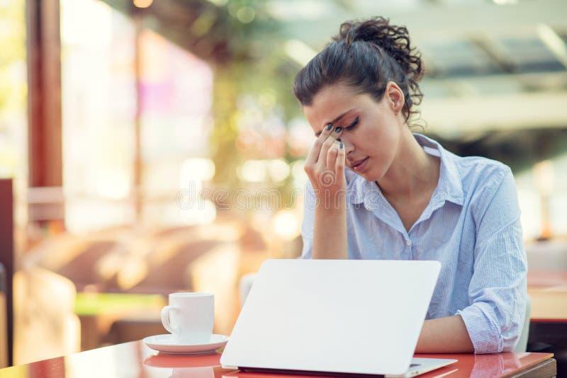 Mujer joven agotadora, jaqueca del dolor de cabeza, dolor de sensaci?n principal del tacto de la mano imagenes de archivo