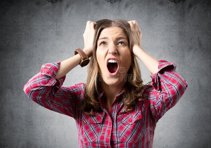 Mujer joven agotadora que grita con pánico imagen de archivo
