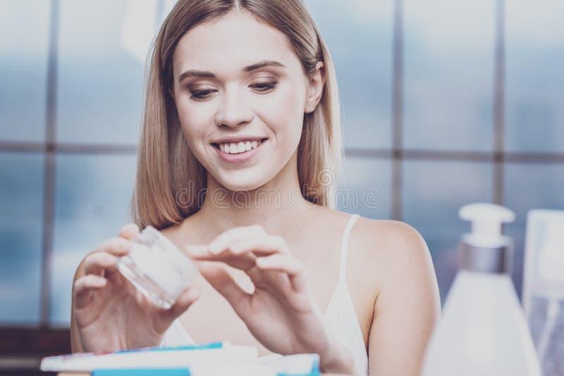 Mujer joven agradable que mira en un tarro de crema de cara foto de archivo libre de regalías