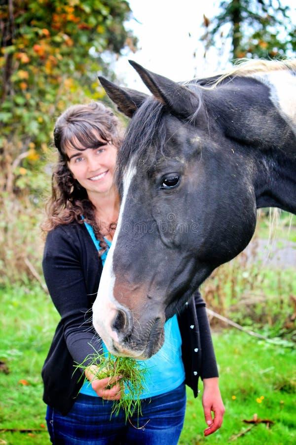 Mujer joven al aire libre alimentando un caballo imagenes de archivo