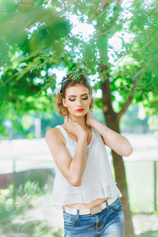 Mujer joven al aire libre en una camiseta blanca y vaqueros, con maquillaje brillante, labios rojos fotografía de archivo libre de regalías