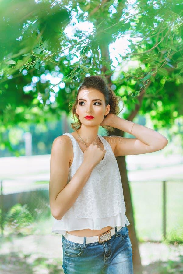 Mujer joven al aire libre en una camiseta blanca y vaqueros, con maquillaje brillante, labios rojos imagenes de archivo