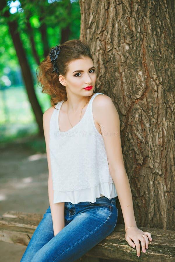Mujer joven al aire libre en una camiseta blanca y vaqueros, con maquillaje brillante, labios rojos Mirada de la cámara fotografía de archivo libre de regalías