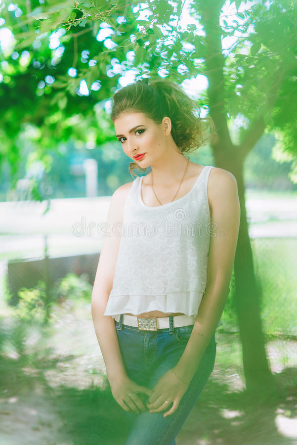 Mujer joven al aire libre en una camiseta blanca y vaqueros, con maquillaje brillante, labios rojos Mirada de la cámara imágenes de archivo libres de regalías