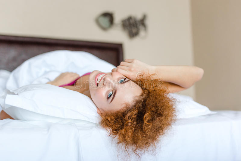 Mujer joven alegre atractiva que miente en cama fotos de archivo